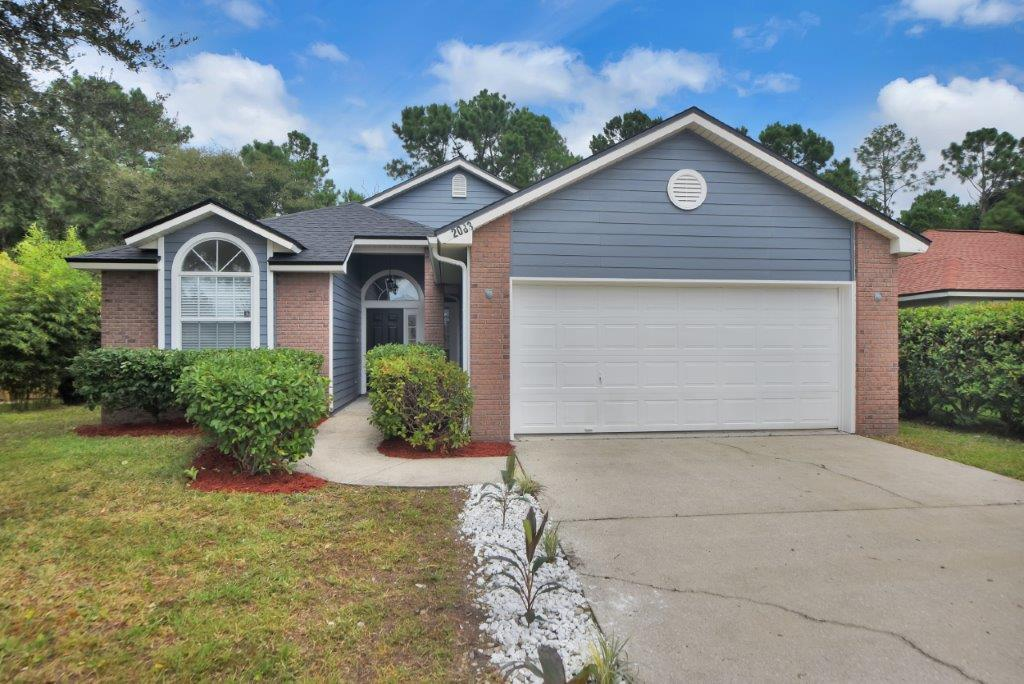 A blue and brick house with a white garage for sale in Jacksonville